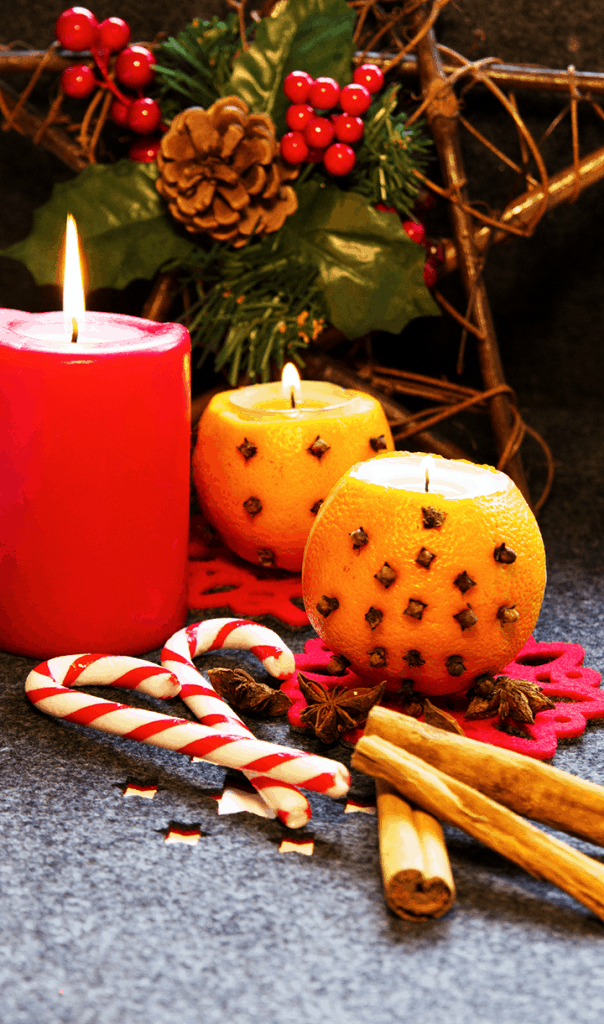 orange and clove pomander candle holder next to a candle and candy cane