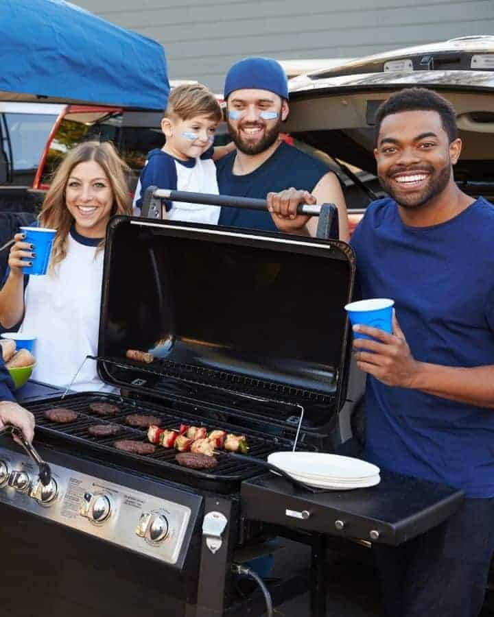 people standing around a grill at a tailgate party at home smiling