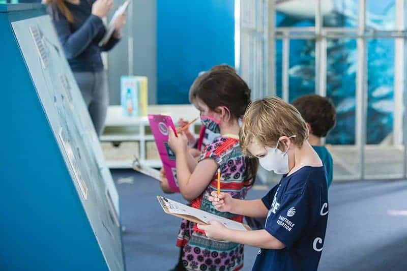 kids doing an indoor scavenger hunt as covid birthday ideas