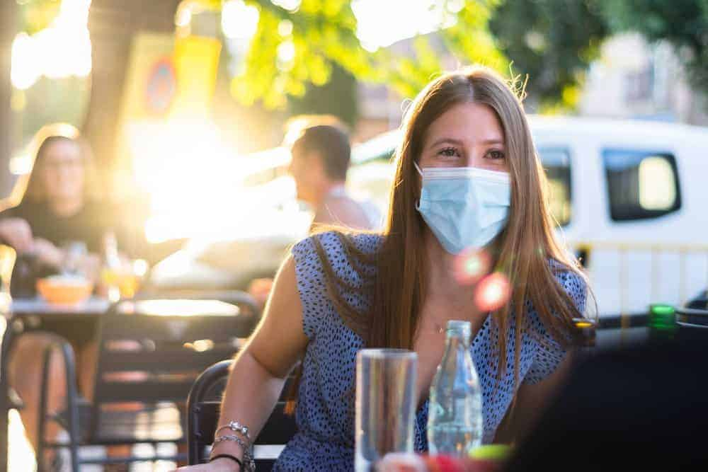 woman sitting at table wearing a mask waiting for food with others spaced apart in the background at an outdoor party during covid