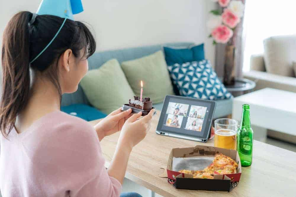 woman holding a cake slice with lit candly while in a virtual birthday party during with friends on a tablet as a covid birthday idea
