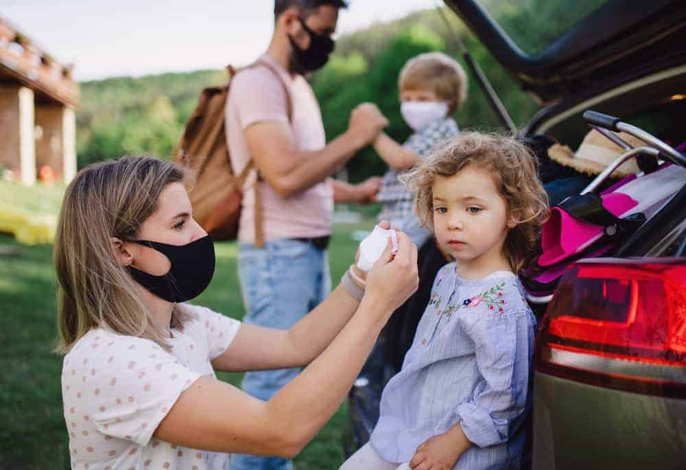 Happy family with two small children by car wearing face masks.