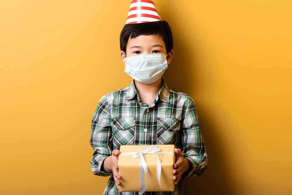 boy wearing a mask and a party hat holding a present during a covid birthda party
