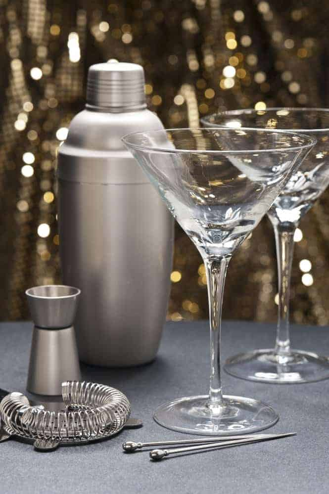 Two Martini glasses with bartender tools in front of gold glitter background