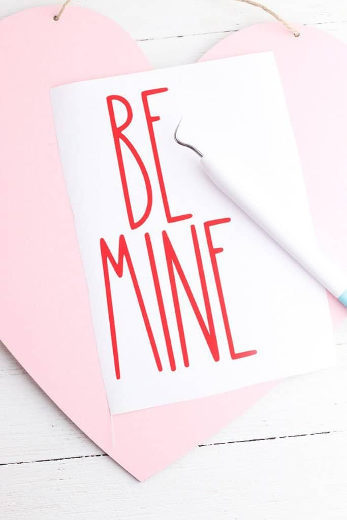 be mine in rae dunn font with wood heart and weeder