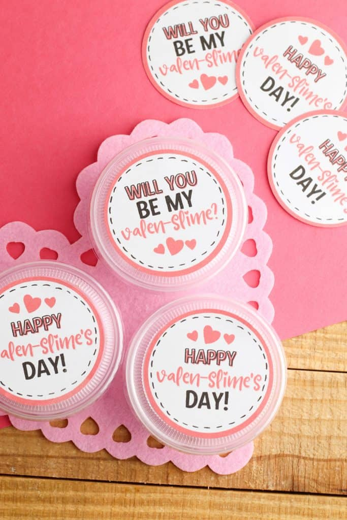 slime valentine with printable gift tags in takeout containers on heart doily
