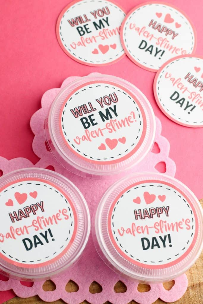 slime valentine with printable gift tags in takeout containers on a pink heart shape doily