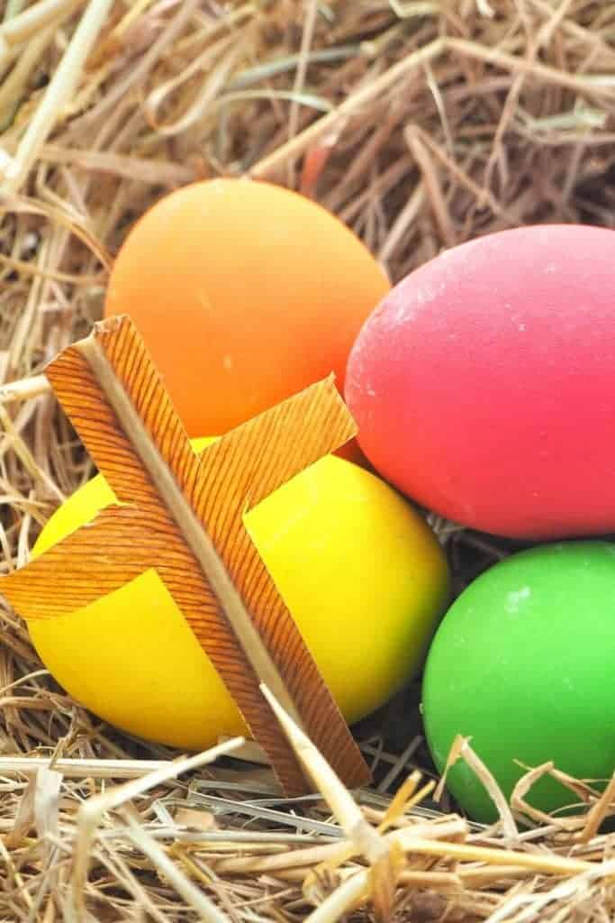 vibrant easter eggs in straw with cross next to them
