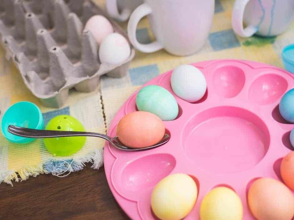 circle egg holder full of dyed easter eggs with dye cups in background
