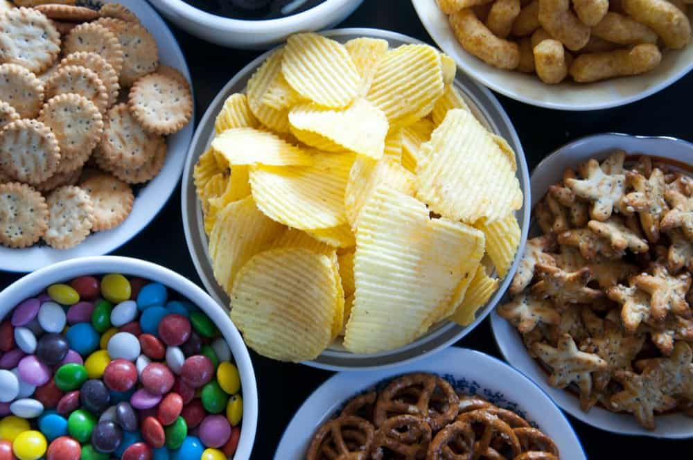 bowls of simple party snacks for kids birthday parties, including chips, crackers, candy, pretzels, and puffs