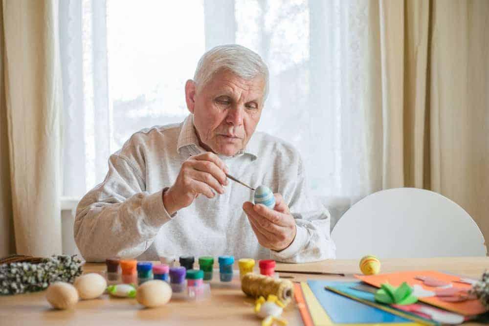 senior man painting wooden easter eggs