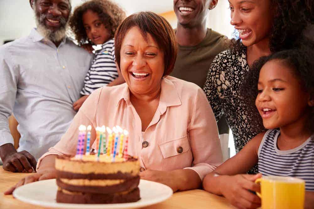 grandma smiling at birthday cake with family surrounding her
