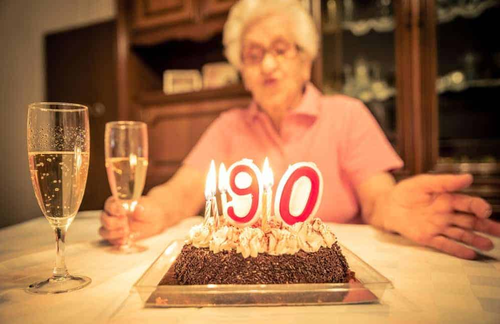 Grandmother sitting at table with birthday cake with candles that say 90 with champange glasses