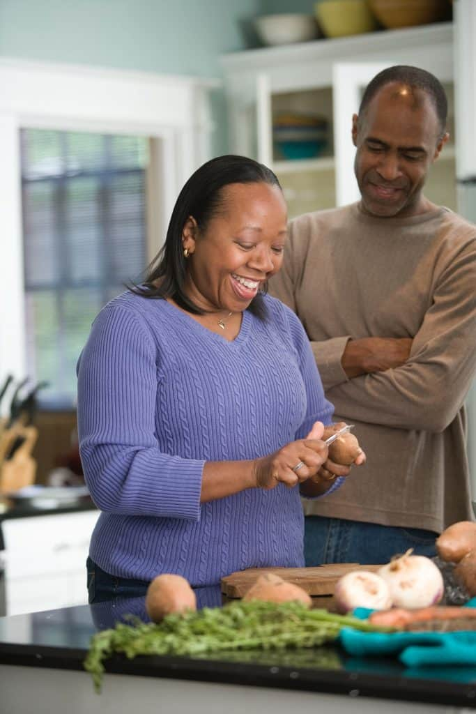 black senior woman cooking in home with male smiling behind her