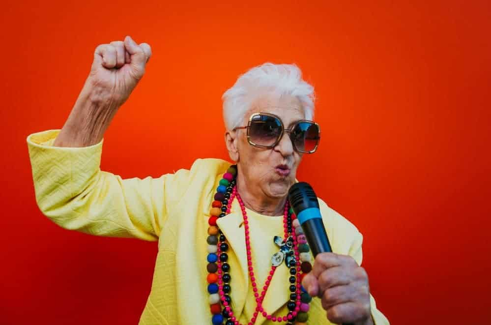 grandmother wearing colorful beaded jewelry rocking out in karaoke