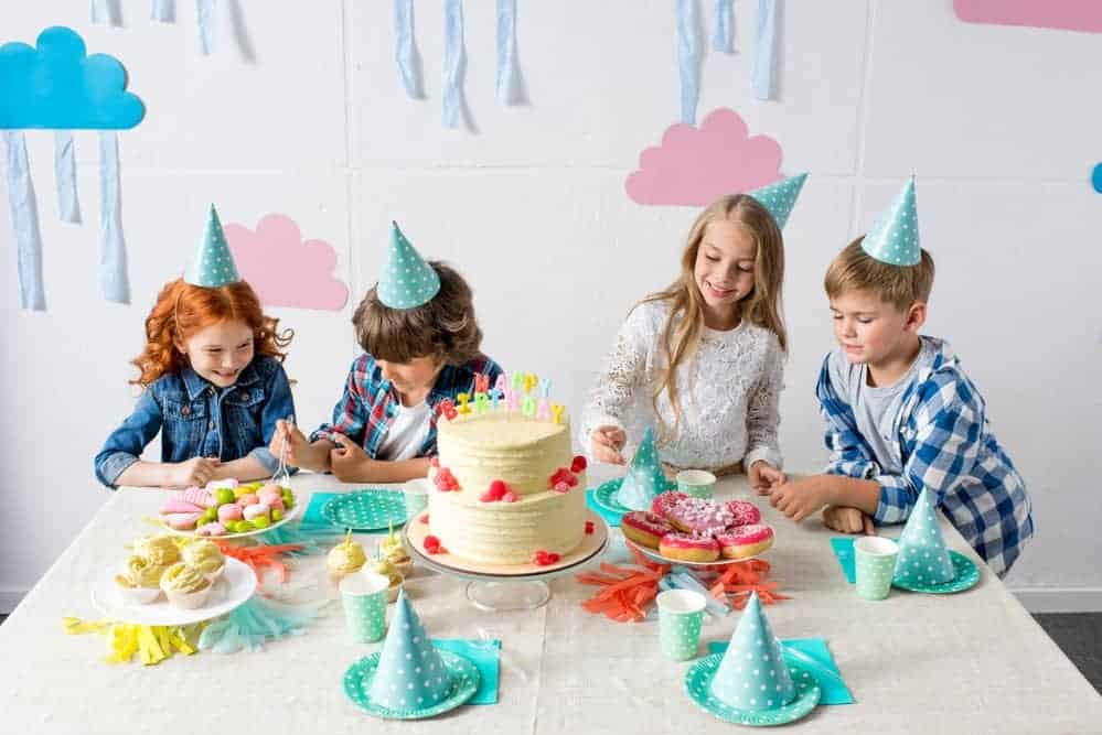 kids enjoying party snacks at a kids birthday party while wearing party hats