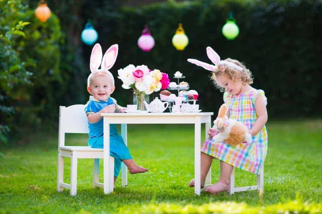 two children having an easter tea party at a table outside
