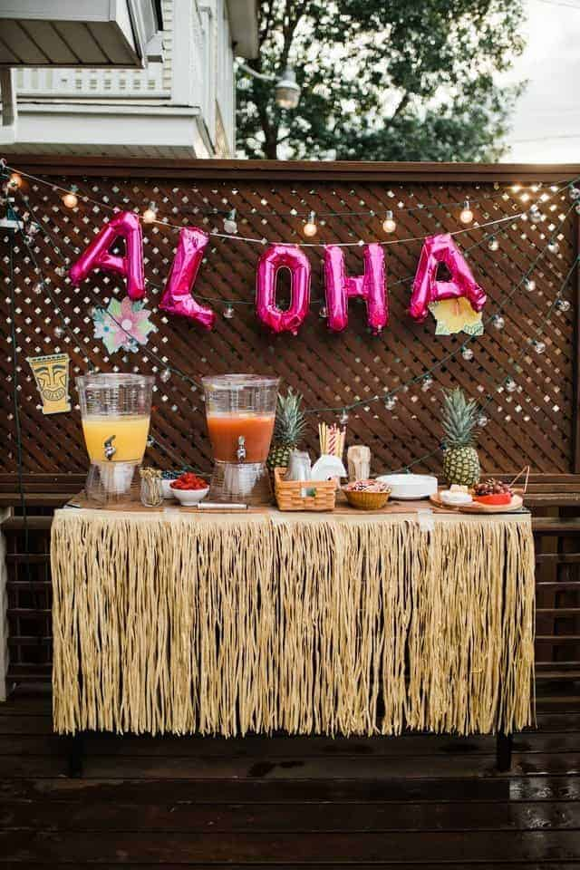 luau party table with aloha balloons in background