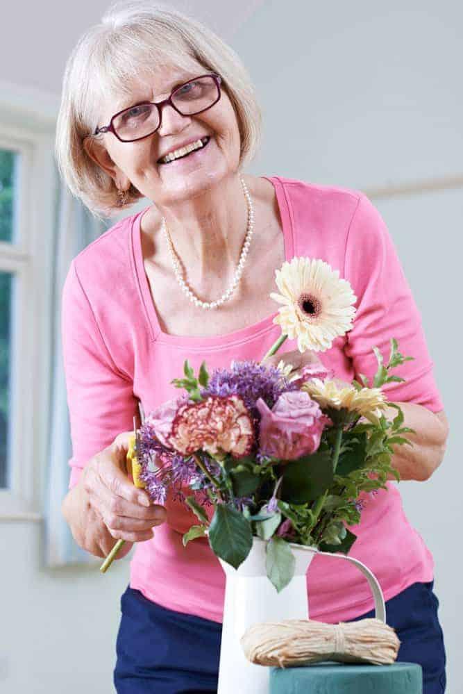 senior woman arranging flowers in a vase