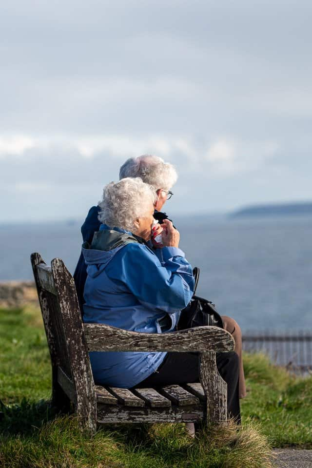 senior citizens sitting on bench overlooking ocean