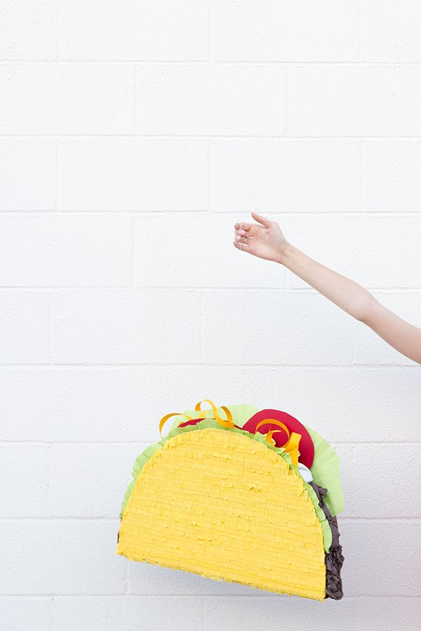 DIY Taco pinata being held by an outstretched arm