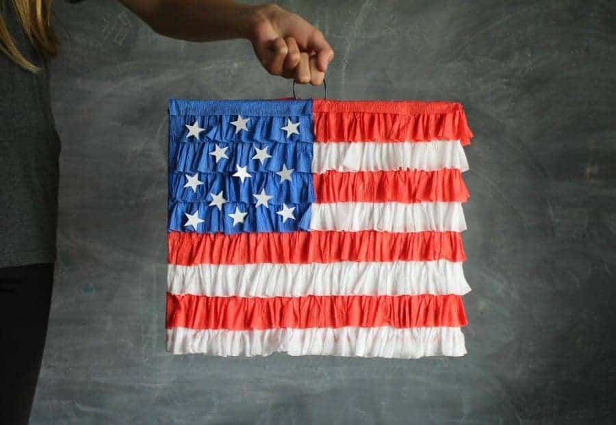 red white and blue flag pinata being held by a hand