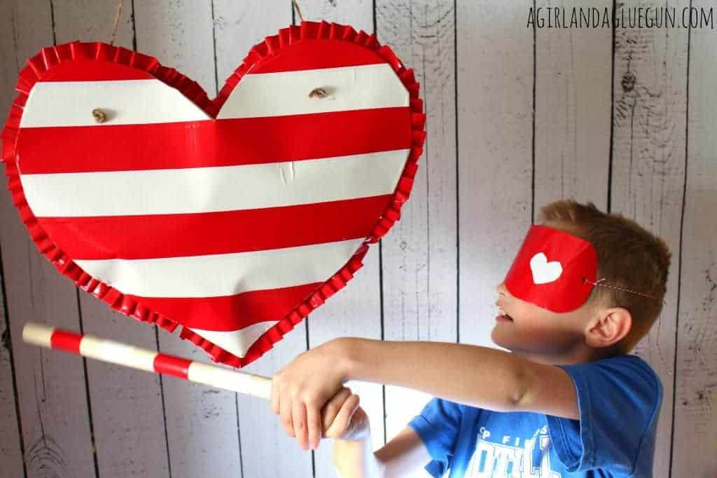 heart shaped pinata made by duct tape and boy wearing a blindfold hitting pinata