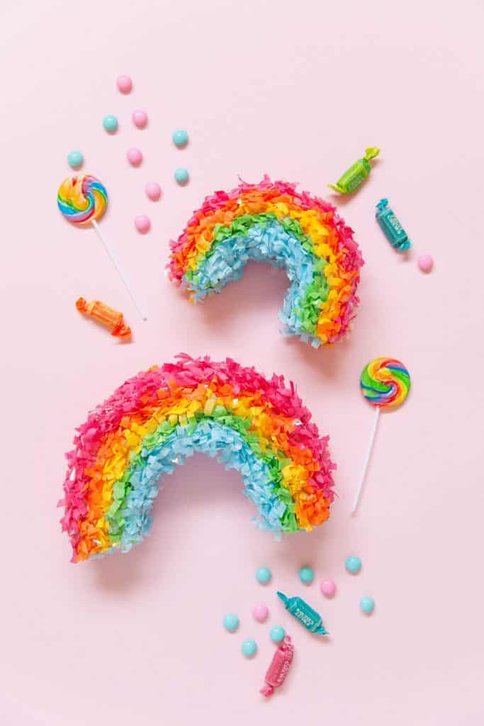 two mini rainbow pinatas with brightly colored candy on pink background