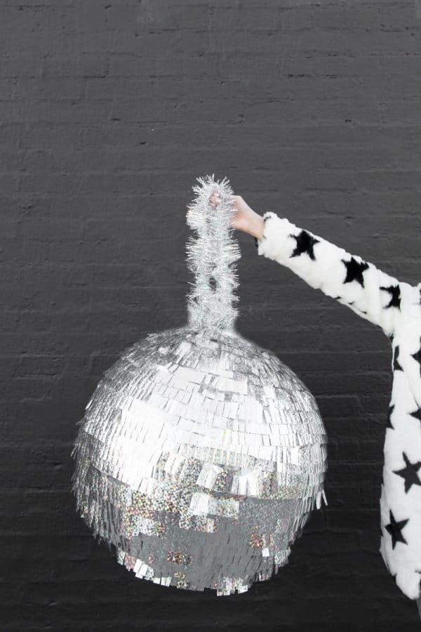 DIY disco ball pinata being held by an arm