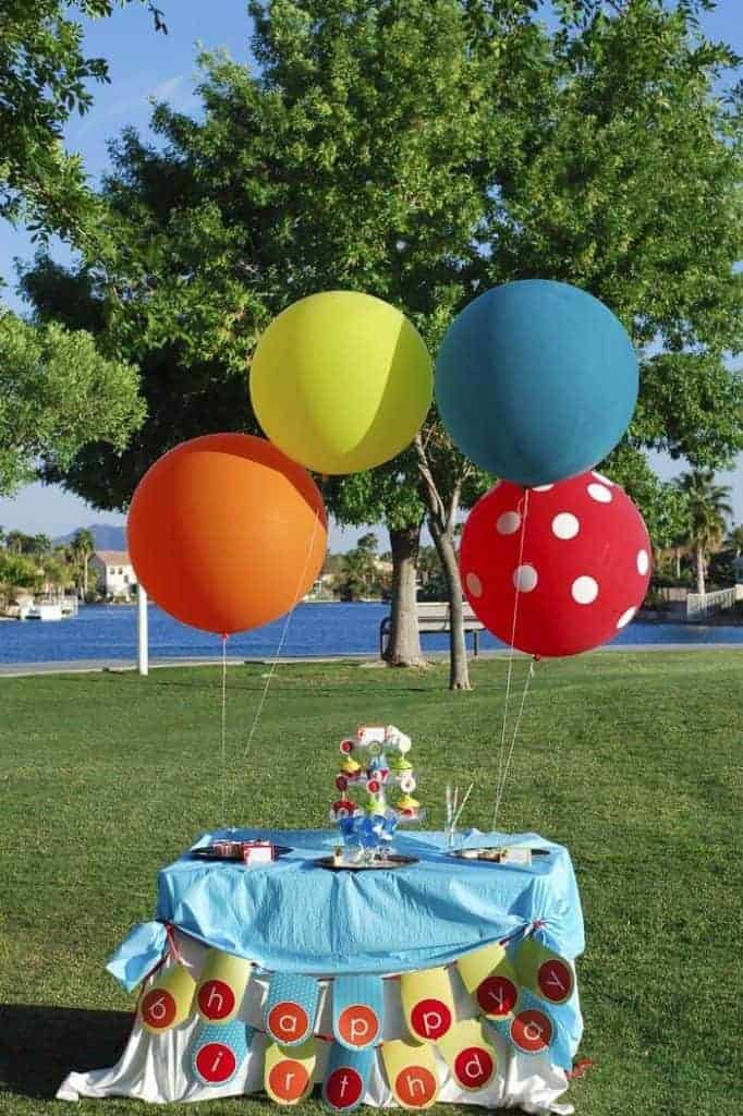 Giant orange, yellow, blue and red polka dot ballons tied to a small party table