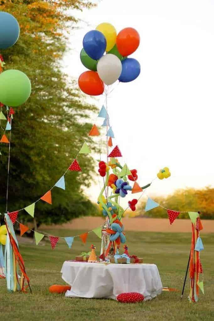 Elaborate party setup with balloons and pennant garland hung in the shape of a circus tents with fancy balloon twists on a pole