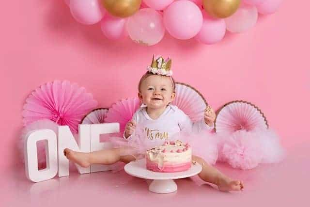 smiling baby with first birthday cake and pink decor