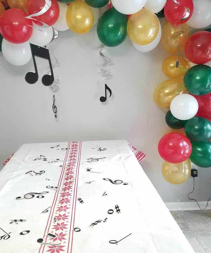 green, red, white and gold balloon garland with music notes hung over table with white linen and musical notes on table