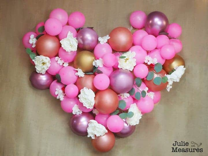 DIY balloon backdrop in a shape of a heart with flowers