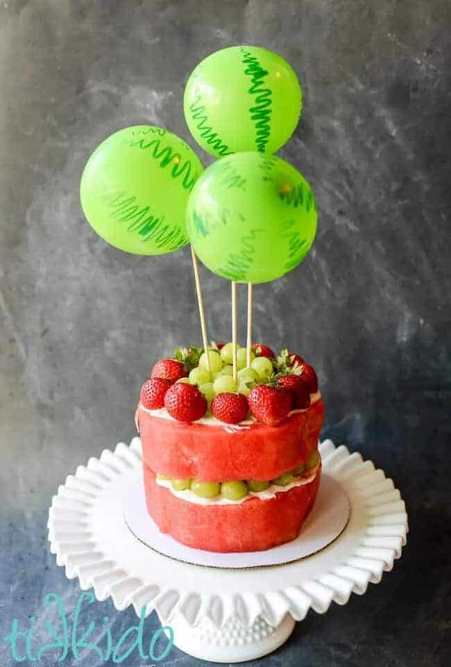 watermelon cake with balloon cake topper on a white cake stand