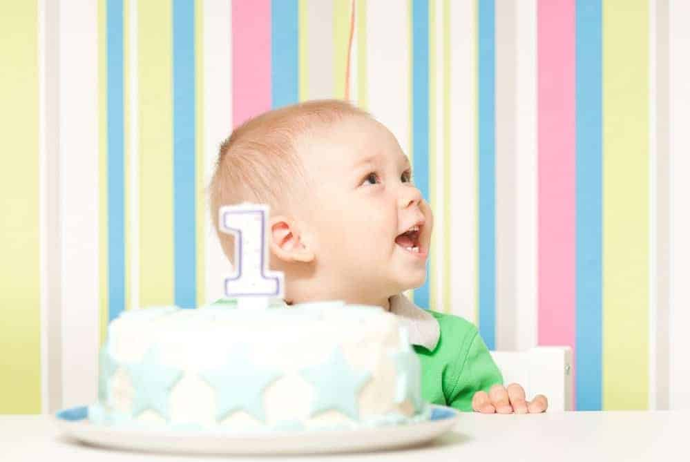 smiling baby in front of striped background with first birthday cake in front