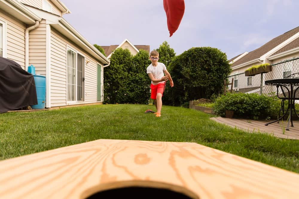 front row view of boy throwing a bean bag to a cornhole board