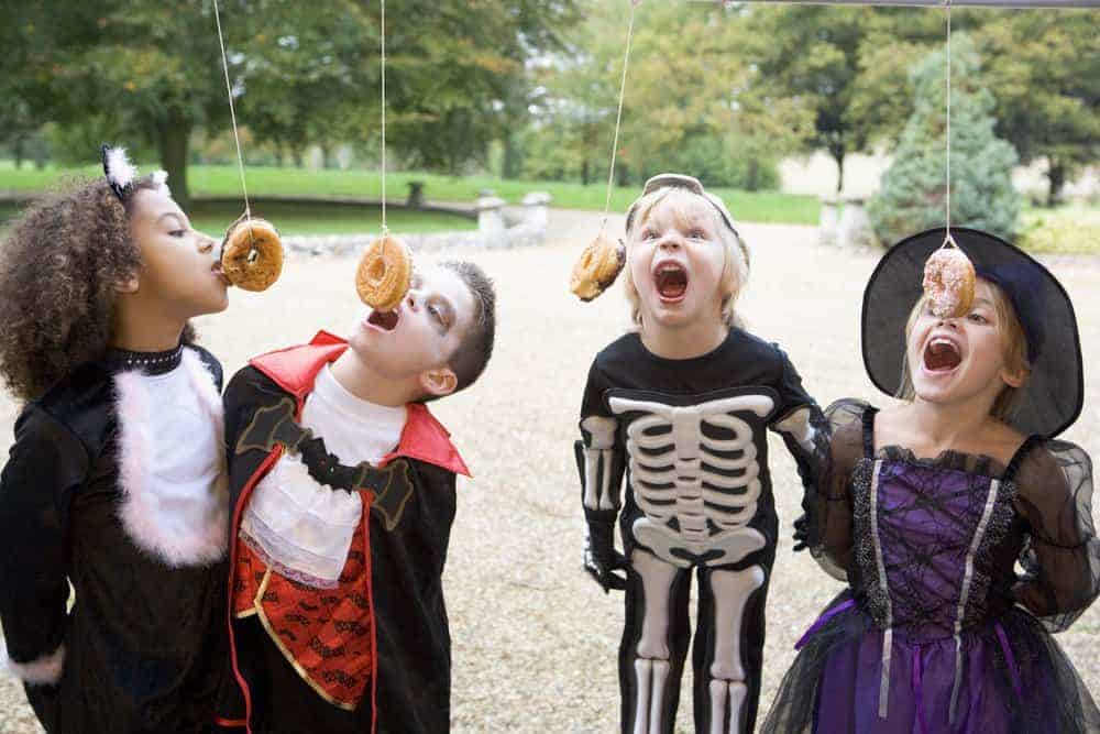 children wearing halloween costumes eating donuts hanging from a string