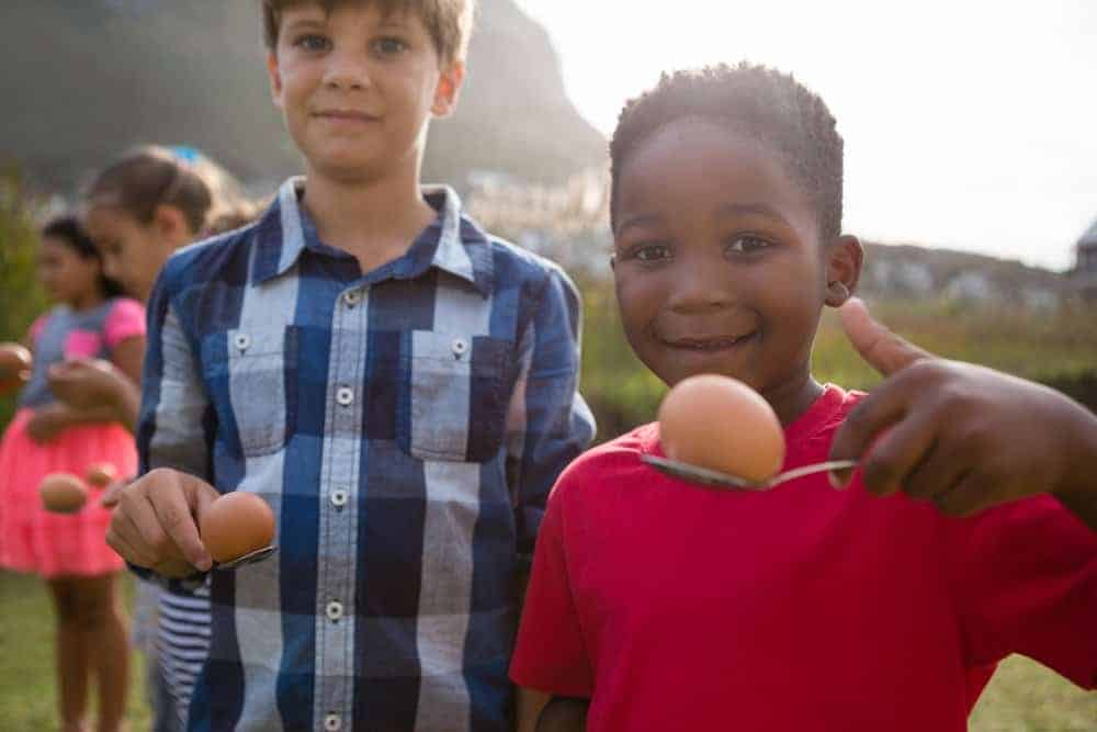 two boys smiling at camera while holding and egg on a spoon for relay race