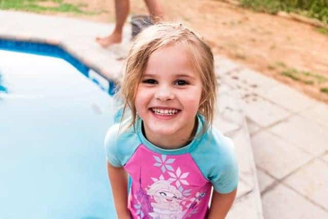 girl smiling standing at edge of swimming pool