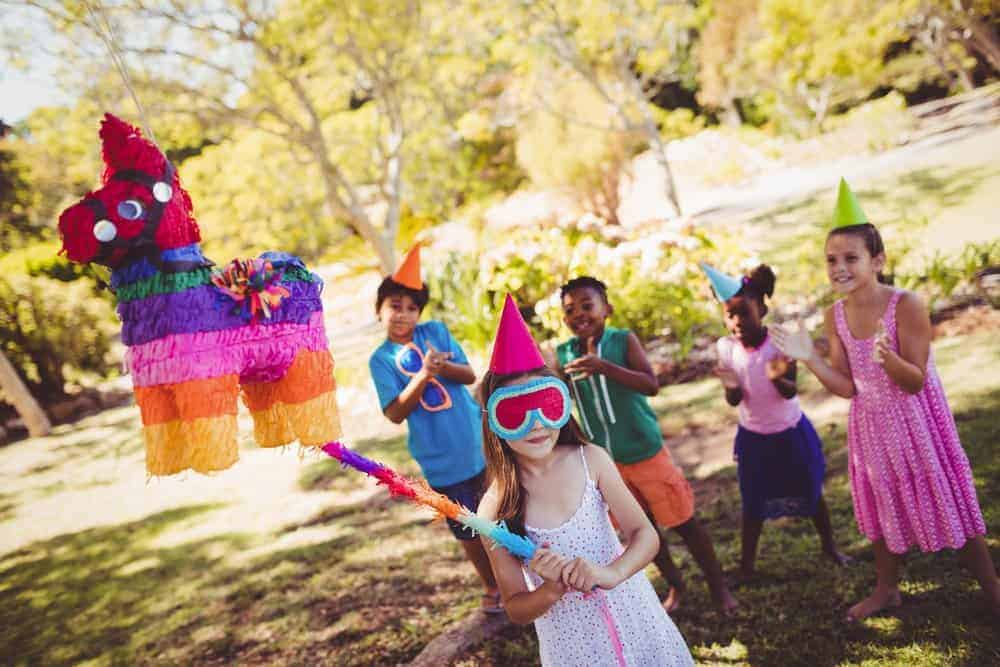 kids at a party cheering on a girl wearing a blindfold getting ready to hit a pinata
