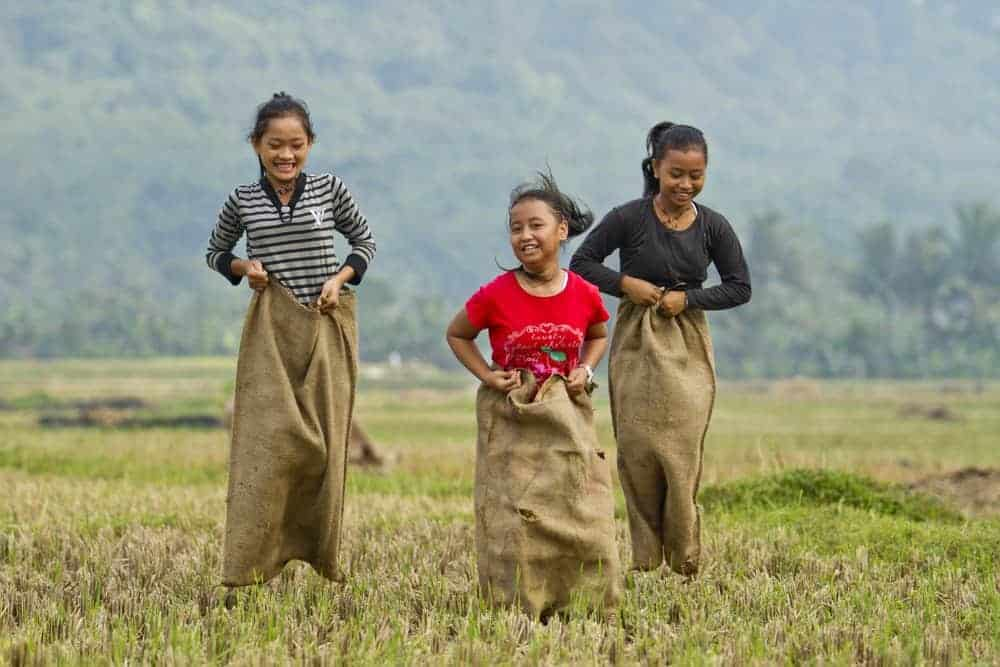 three girls laughing during a potato sack race in field with mountains and trees in background