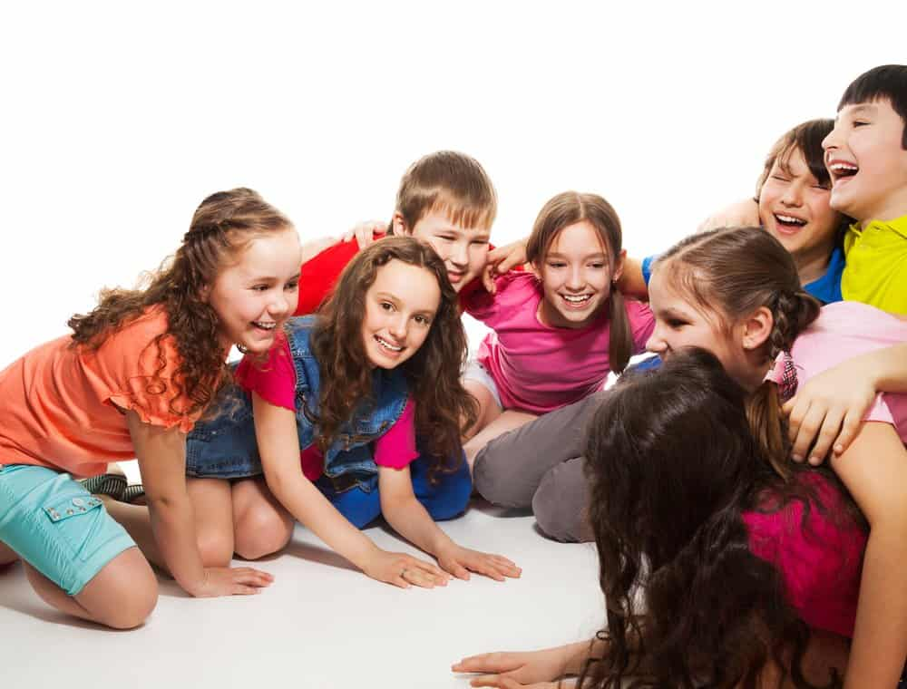 group of tweens crouched on the floor laughing and acting like they are playing a game