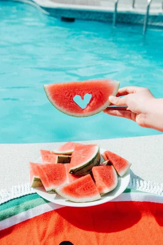 hand holding slice of watermelon with heart cutout over a plate of watermelon slices by pool
