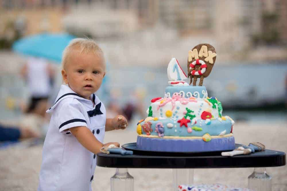toddler baby standing next to a ocean themed birthday cake at a beach birthday party