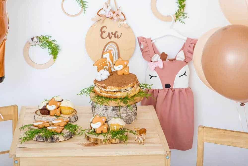 birthday party table setup with swee deer and woodland decor, treats, cookies and a deer dress