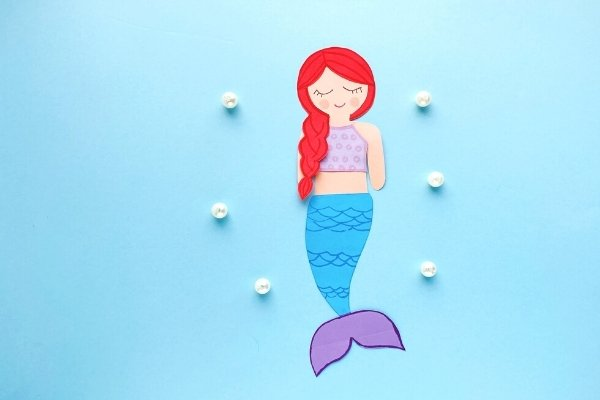 mermaid paper craft made from a free printable mermaid template on a blue background with white pearls