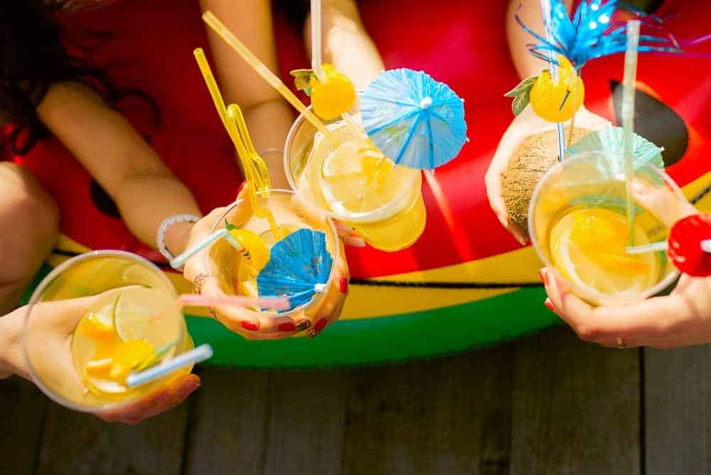 overhead shot of summer cocktails being held by hands with summer party decorations in cups