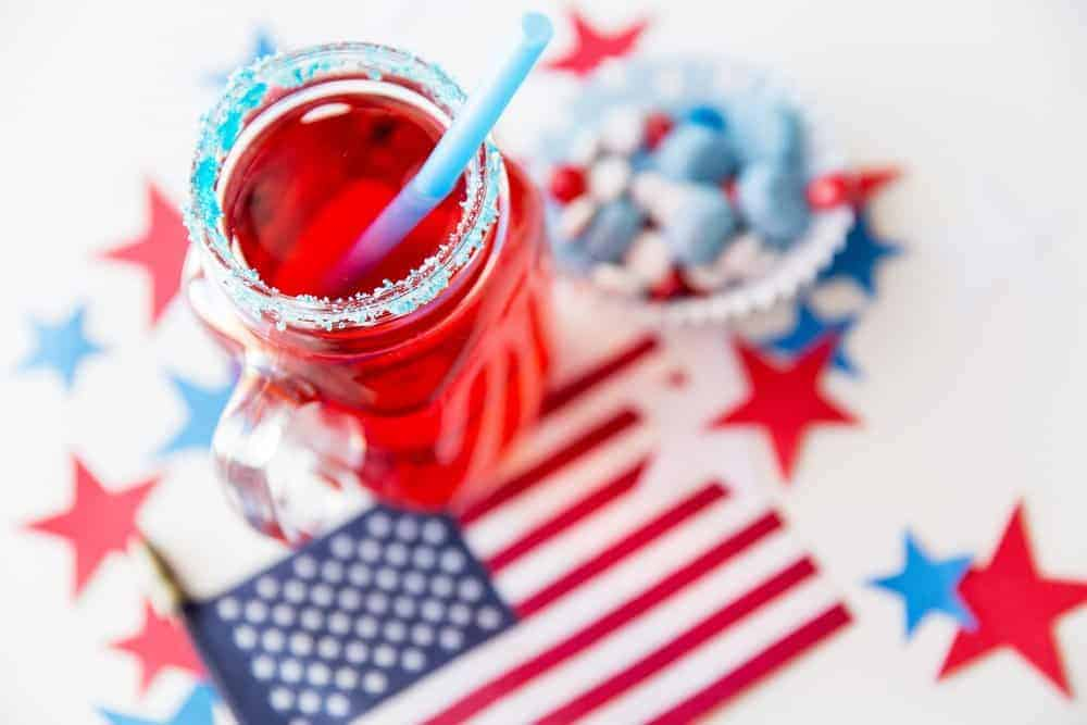 red drink in mason jar with blue sugar and straw on top of american flag and patriotic decor