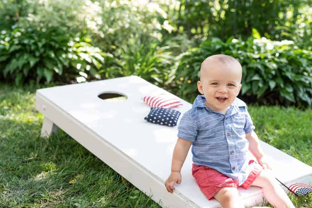 boy in patriotic colors sitting on a white corn hole aord with stars and stripes beanbags